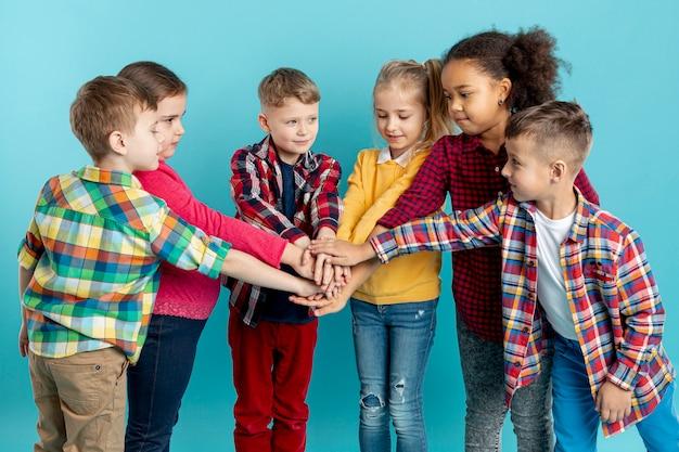 Группа детей делает рукопожатие