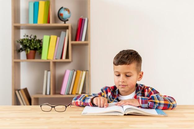 Вид спереди маленький мальчик, чтение