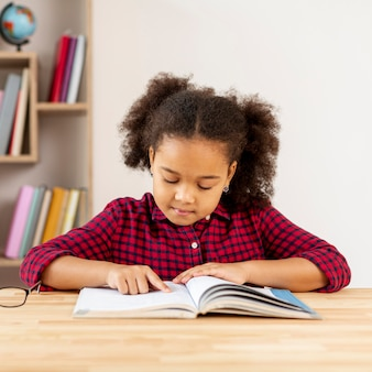 Вид спереди маленькой девочки, читающей