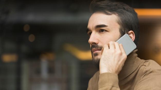 Боковой вид деловой человек разговаривает по мобильному