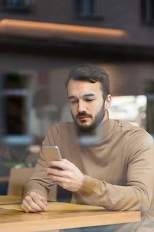 モバイルを見て高角の若い起業家