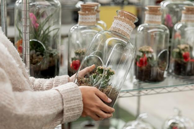 透明な瓶を保持しているクローズアップの花屋