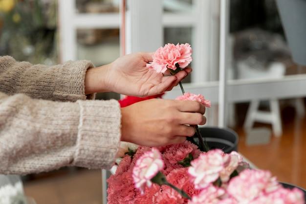 ピンクの花を保持しているクローズアップの女性