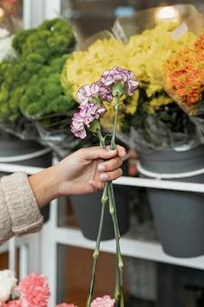 美しい花を保持しているクローズアップの女性