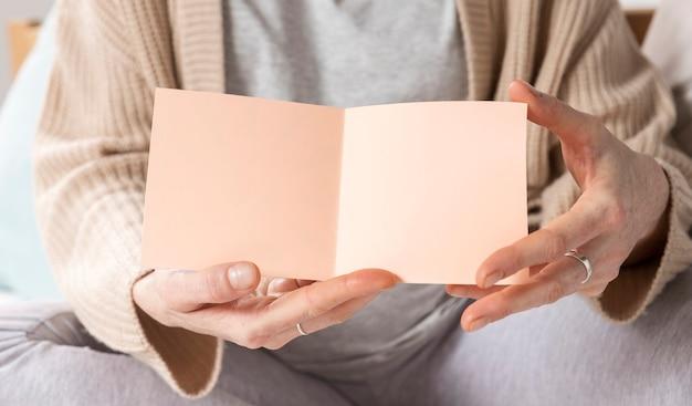 グリーティングカードを持つクローズアップ女性