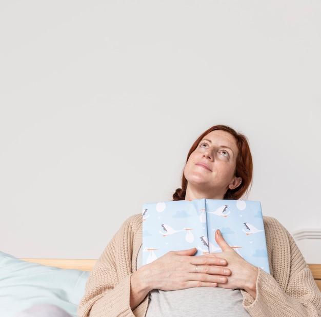 赤ちゃんの本を読んでコピースペース妊娠中の女性