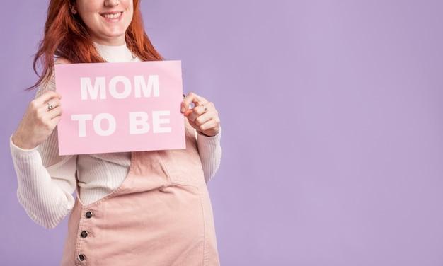 メッセージになるママと紙を保持しているクローズアップの妊娠中の女性
