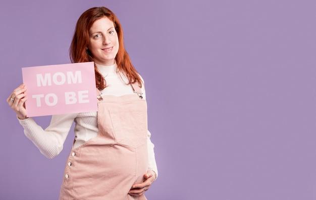 メッセージであるママと紙を保持しているコピースペース妊娠中の女性