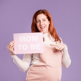妊娠中の女性がメッセージであるママと紙を指して