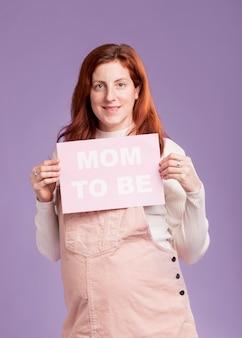 メッセージであるママと紙を保持している正面妊娠中の女性