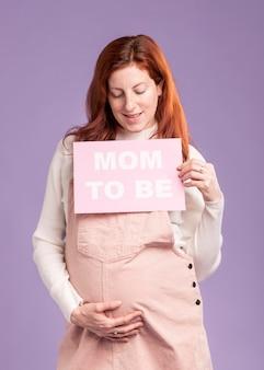 メッセージであるママと紙を保持しているローアングル妊娠中の女性
