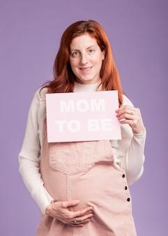 メッセージであるママと紙を保持している低角度の妊娠中の女性