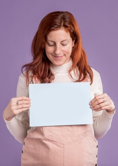 オーブンメッセージで赤ちゃんと紙を保持している妊娠中の女性