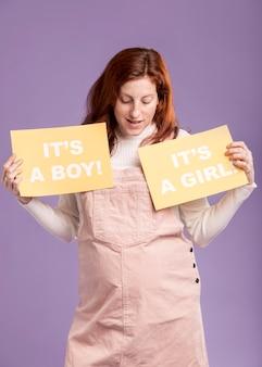 Низкий угол беременная женщина, держащая бумагу с полом ребенка