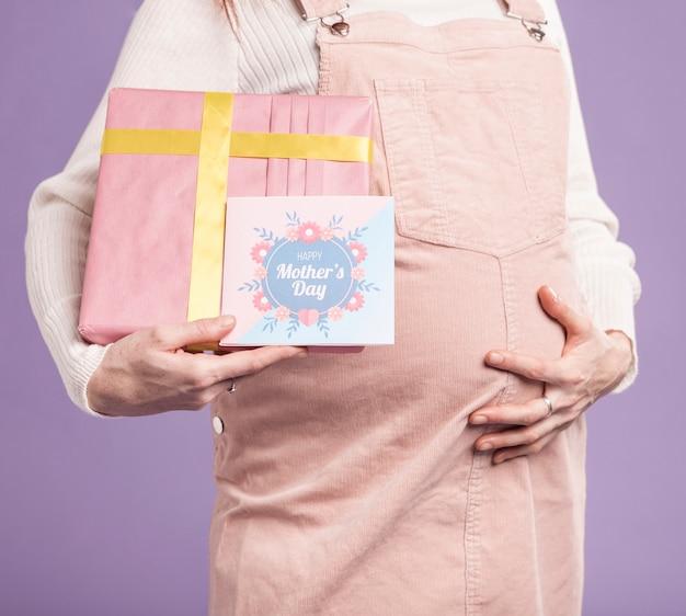 Крупным планом беременная женщина, держащая подарок и поздравительную открытку