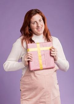 Высокий угол смайлик женщина, держащая подарок
