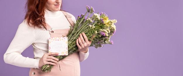 Крупным планом беременная женщина, держащая букет цветов