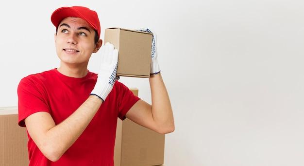 パッケージを運ぶコピースペース若い配達人