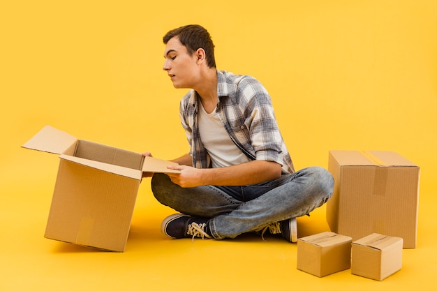 Низкий угол доставщик проверяет упаковочные коробки