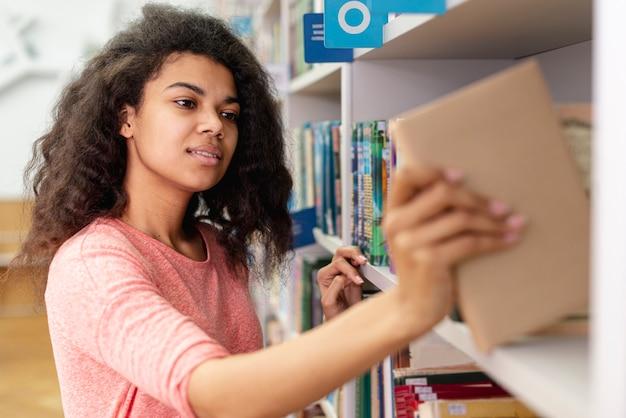 Девочка-подросток помещает книгу на книжную полку