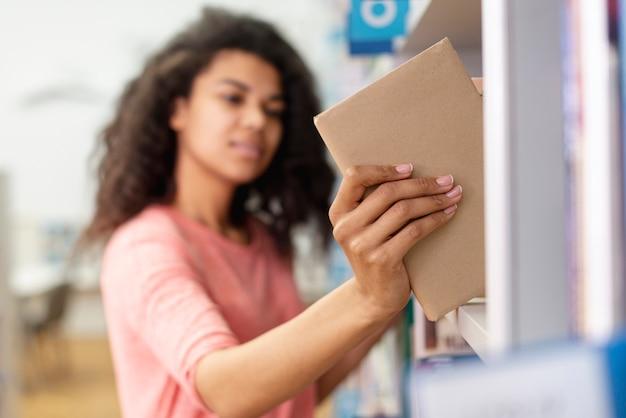 本棚に本を置くぼやけている女の子
