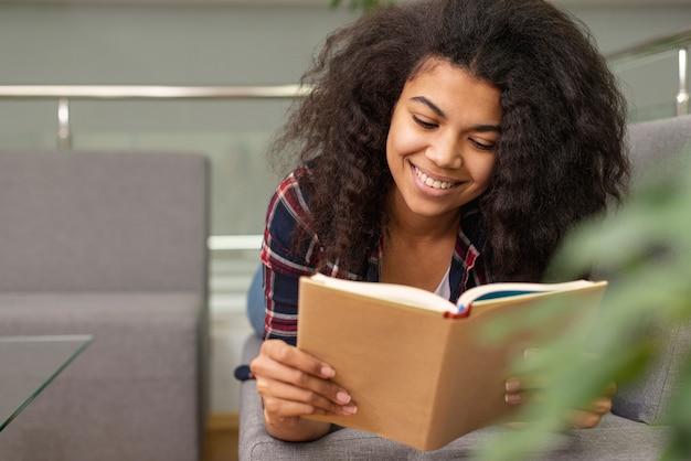Низкий угол смайлик девочка-подросток, чтение