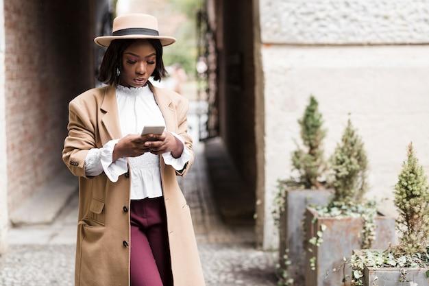 Смайлик модная женщина смотрит на свой телефон с копией пространства