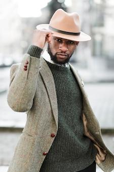 屋外でポーズの帽子を持つ男