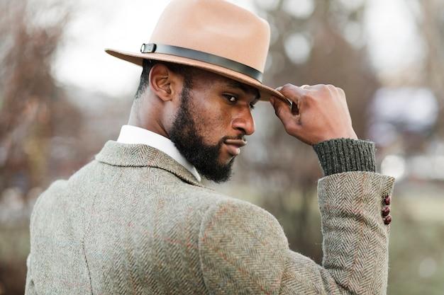 外でポーズの帽子を持つサイドビュー男