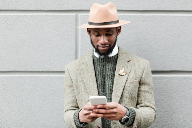 ハンサムな男が彼の電話でソーシャルメディアをスクロール
