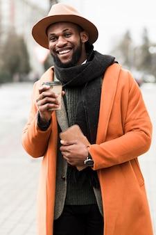 Человек вид спереди в оранжевом пальто держит чашку кофе снаружи