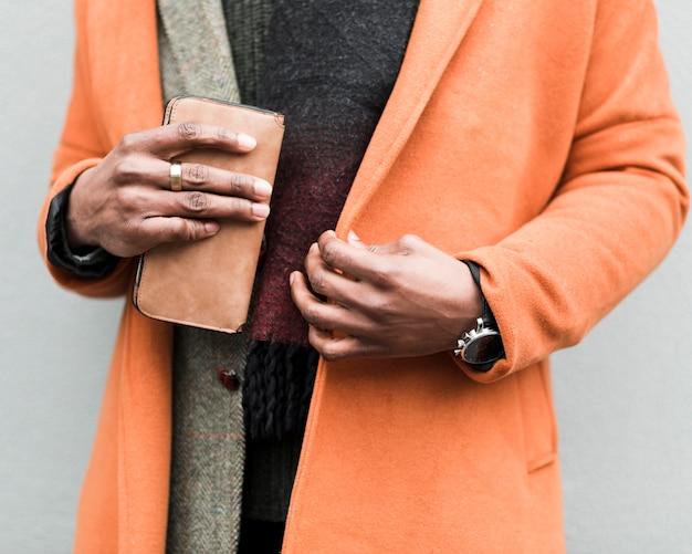 Мужчина в оранжевом пальто держит свой кошелек