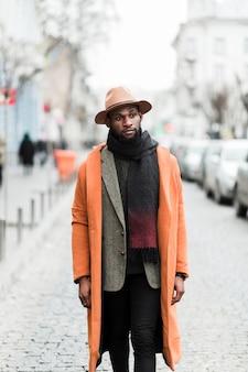 オレンジ色のジャケットのポーズでハンサムな男