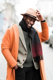 屋外でポーズオレンジジャケットでハンサムな男