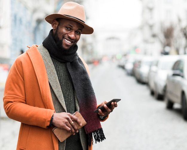彼の携帯電話を保持しているオレンジ色のジャケットでハンサムな男