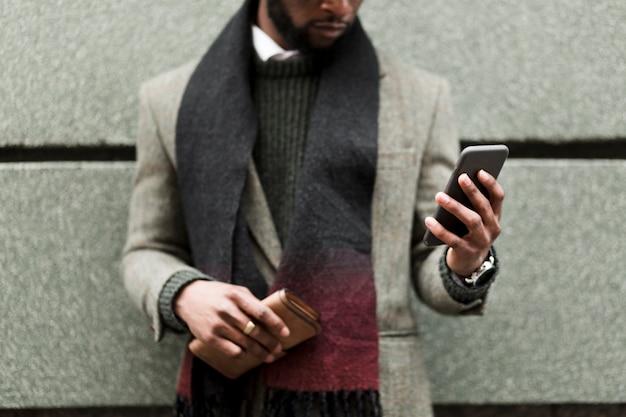 Вид спереди человек в серой куртке держит свой телефон