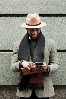 彼の電話で見ている灰色のジャケットの正面男