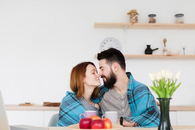 男と女が毛布で台所に座って