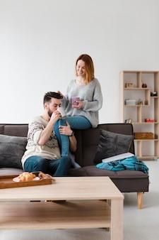 朝のコーヒーを飲むのリビングルームのカップル