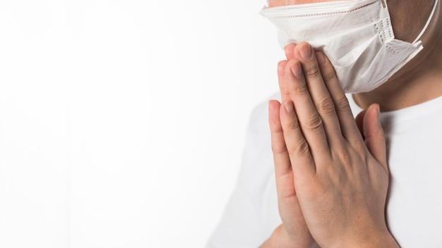 Вид сбоку больного пациента с медицинской маской молиться