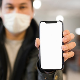 Расфокусированным человек с медицинской маской, подняв телефон