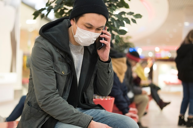 Вид сбоку человека с медицинской маской, разговаривает по телефону в торговом центре
