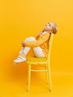 見上げながら椅子でポーズの女の子の側面図