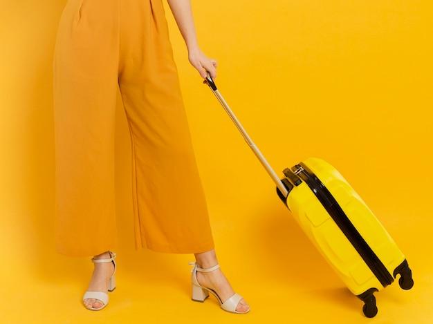 Женщина на каблуках держит багаж
