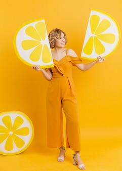 女性がレモンスライスの装飾を押しながらポーズ