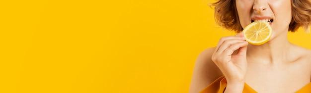 レモンのクローズアップを食べる女性