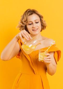 スマイリー女性注ぐレモネード