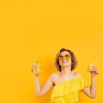 レモネードのガラスを保持しているサングラスをかけたスマイリー女性