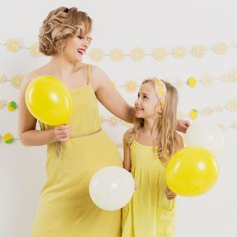 Вид спереди женщины и девушки позируют с воздушными шарами