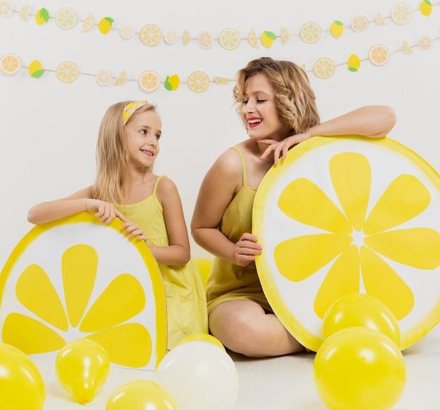 幸せな女とレモンの装飾でポーズの女の子